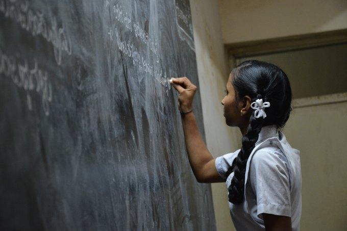 Indian girl writing on chalkboard