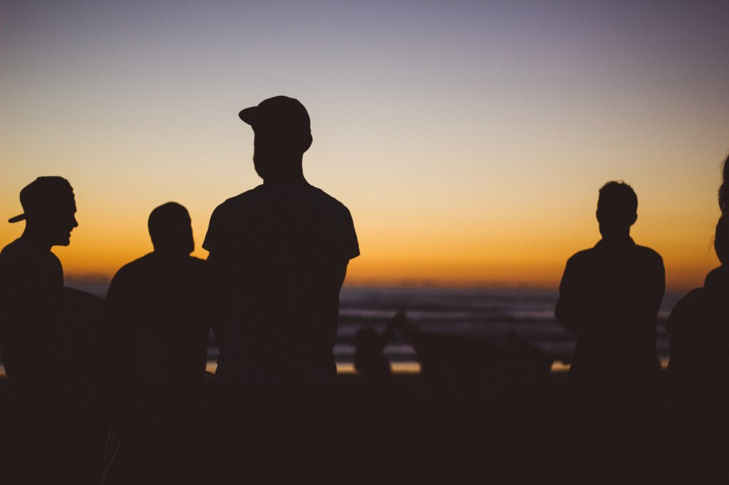 silhouettes of men in front of the sunset