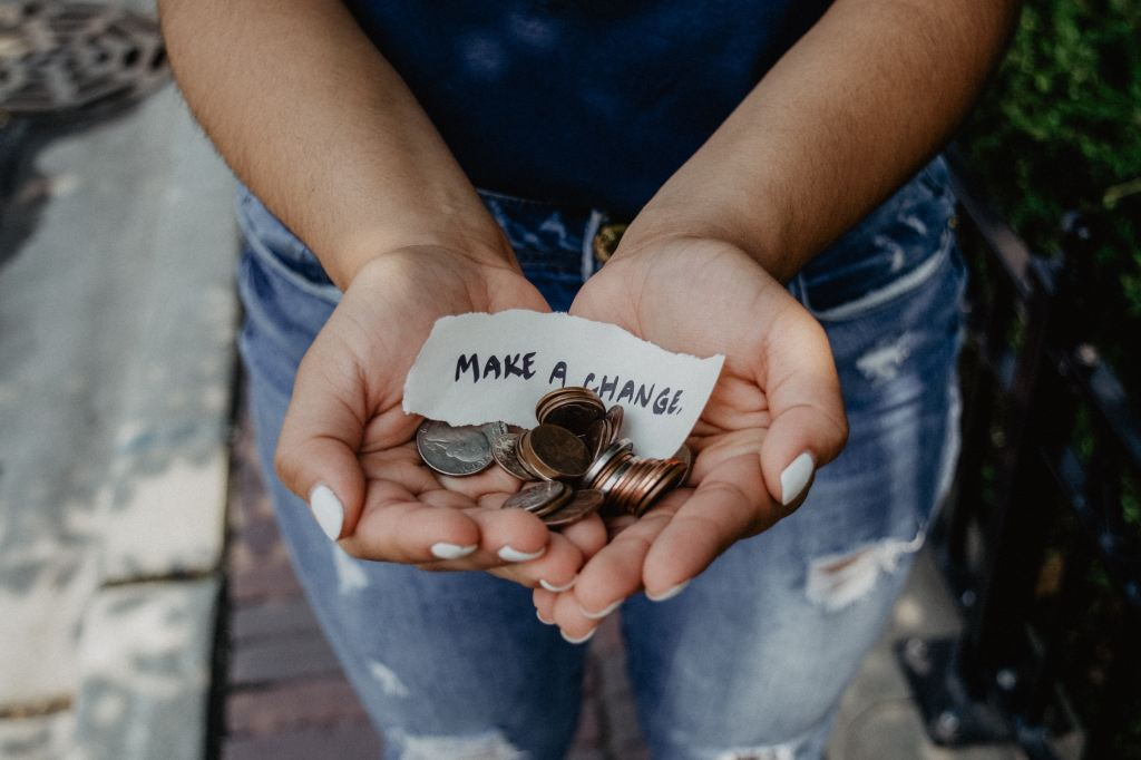 hands holding coins and a sign that says 'make a change'